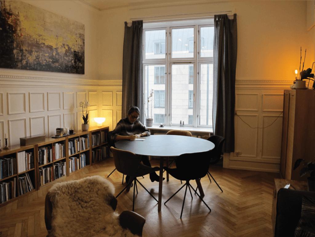 Psykolog Mette Kyung siddende ved et bord på kontoret
